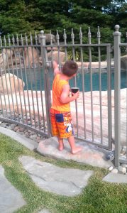 Boy Trying To Get Into Gated Pool